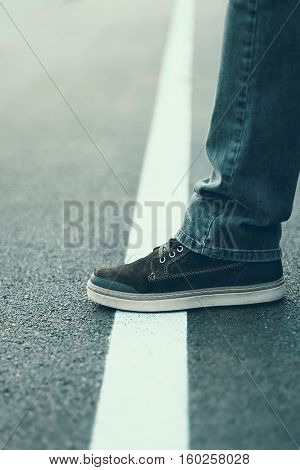 Male Foot Standing On The White Line. Crossing Line Concept.