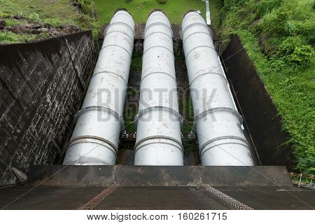Large water pipe in a sewage treatment plant with digestion tanks in the background top view.