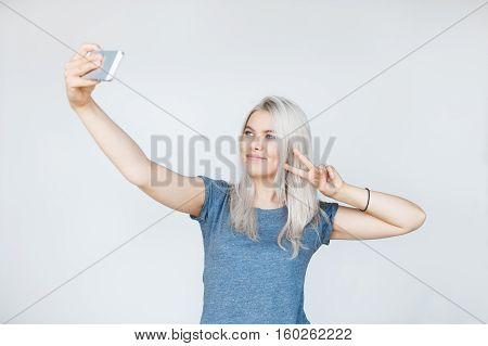 Pretty hipster girl taking selfie and smiling. Showing two fingers peace sign isolated over white background