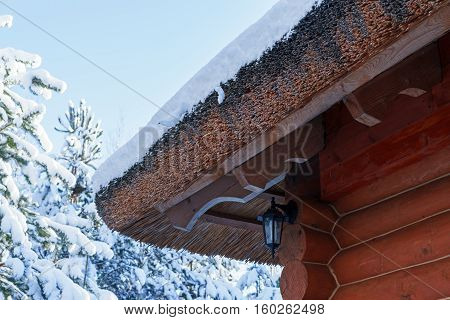 Wooden log thatched roof, covered in snow in winter