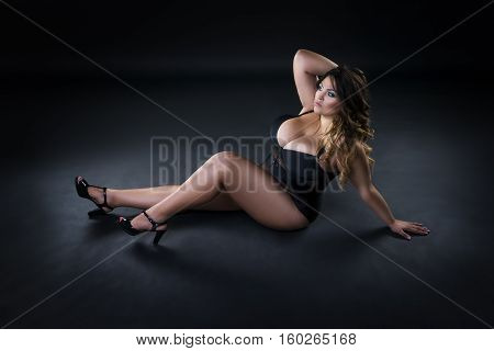 Young beautiful plus size model in underwear xxl woman on black background full length portrait