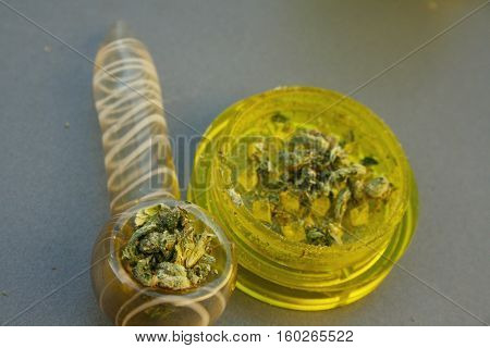 Grinder with pipe and marijuana ready to medicate