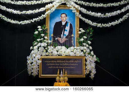 November 29 2016. White flowers and golden pedestals decorate a picture of King Bhumibol Adulyadej in the traditional academic dress of Thammasat University Ta Prachan campus. Bangkok Thailand.