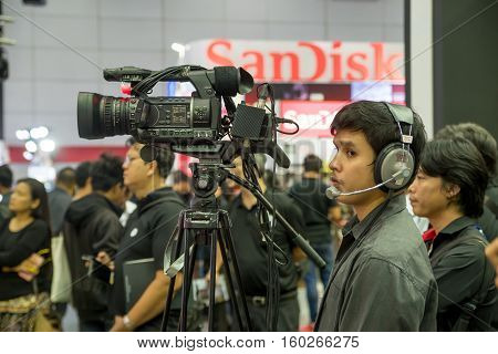 December 2 2016. A camera operator stands next to his video camera while recording a show at a consumer electronics exhibition. Bangkok Thailand.