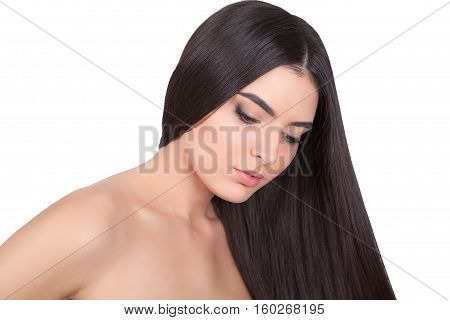 Young beautiful girl with long hair and bare shoulders looks to the down.