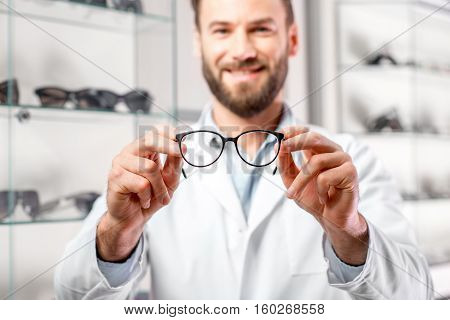 Handsome ophthalmologist holding eyeglasses for a try out. Optometrist offering to wear a pair of glasses. Image with small deph of field focused on the hands and glasses