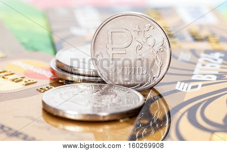 MOSCOW, RUSSIA - NOVEMBER 27, 2016: Russian rubles coins over different credit cards close up