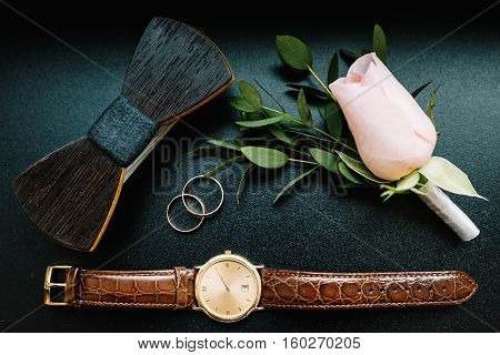 Groom accessories. Watches, gold wedding rings, wooden bow tie and boutonniere on a black background