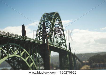 Beautiful Oregon Coast Bridge. Yaquina Bay Bridge in Newport, Oregon, USA. Sunny day with blue sky and clouds. Captured with tilt-shift lens.