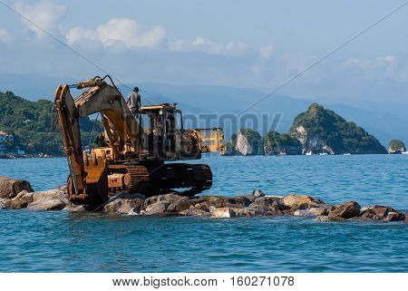 An excavator on a pile of rocks out on the ocean