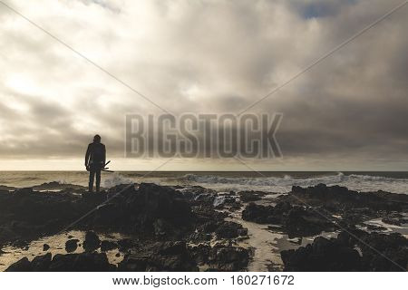 A photographer holds a tripod while looking out over the ocean at Cape Perpetua on the Oregon Coast. Pacific Northwest USA.