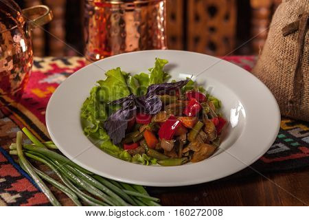 Saute Vegetables With Basil And Lettuce On A White Plate