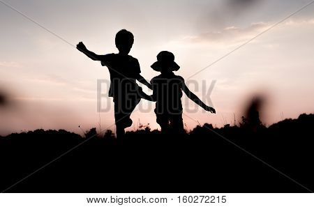 Silhouettes of kids jumping off a hill at sunset. Little boy and girl jump raising hands up high. Brother and sister having fun in summer. Friendship freedom concept. Fraternal twins on vacation in mountains.