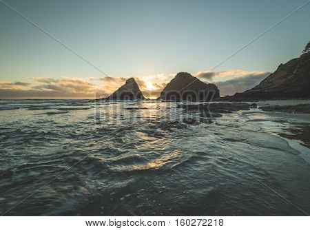 Tide rolling in on a beautiful beach with two rock stacks and a mountain in the background.