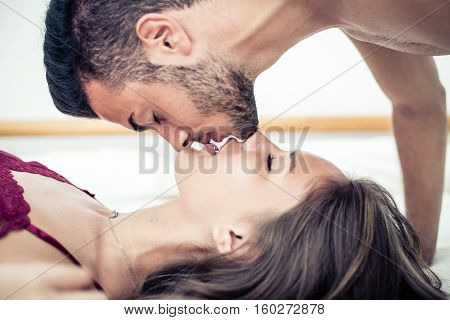 Couple kissing in bed. Romantic passion and love in bed