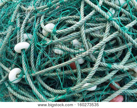 LUARCA SPAIN - DECEMBER 4 2016: Green fishing net with white floats at the fish market pier in Luarca Spain.