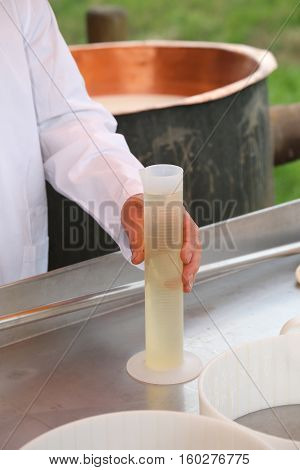 cheesemaker takes a plastic tube with the rennet to production cheese on the farm