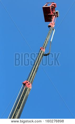 hydraulic arm with the metal basket of an aerial platform to the maximum extension