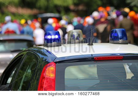 Police Car With Blue Sirens In The Street Escorting Participants
