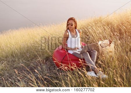 Young brunette girl in sunglasses on beanbag with laptop. Hipster freelancer woman works outdoors in meadow. freelance concept