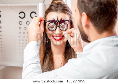 Ophthalmologist wearing try-on tool for vision check to the young female patient in front of the eye chart in the cabinet. Eye doctor with patient in the clinic