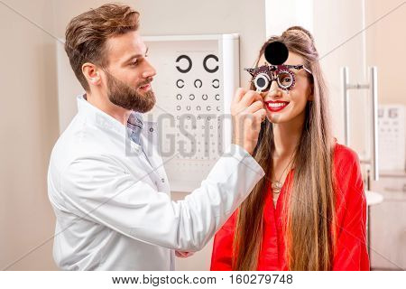 Ophthalmologist checking vision of the young woman with try-on tool and eye chart in the cabinet