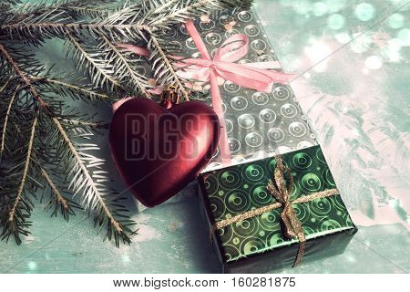 Wrapped in paper Christmas gifts and green fir branch on a light background
