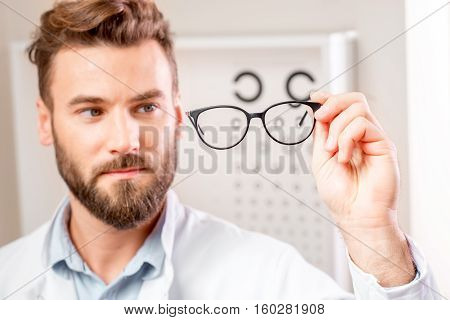 Handsome ophthalmologist looking at the glasses in front of the eye chart in the cabinet. Image with small deph of field focused on hands and glasses