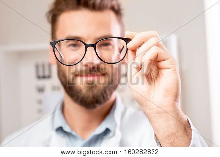 Handsome ophthalmologist looking through the glasses on the eye chart background in the cabinet. Image with small deph of field focused on hands and glasses