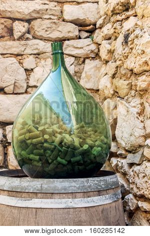 wine corks in a big glass bottle
