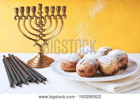 Hanukkah menorah and sufganiot on the table horizontal