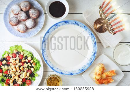 Traditional Hanukkah dishes on the white wooden table top view