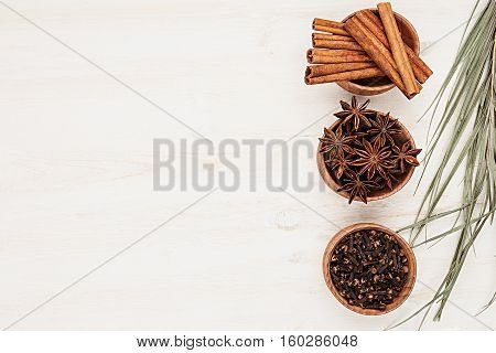 Spices - aniseed cinnamon cloves and herbs in wooden bowls on a wood white background. Spicy seasonings for cooking. Top view.