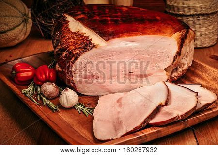 Christmas smoked gammon chopped slices on wooden board with spices. Rustic style.