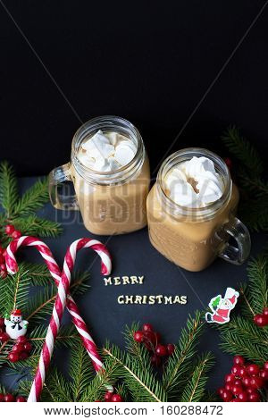 hot cocoa and candy marshmellow on the background of trees. The inscription Merry Christmas