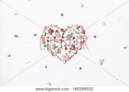 Flowers composition. Heart symbol made of dried flowers and leaves. Top view flat lay