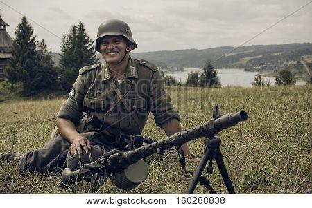 PERM RUSSIA - JULY 30 2016: Historical reenactment of World War II summer 1942. German soldier with machine gun