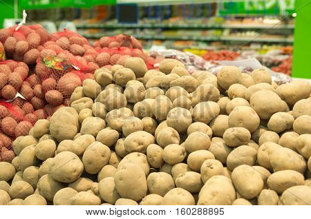 Close up of white and sweet potatoes on market stand. Fresh organic on shelf in supermarket. Healthy food concept. Vitamins