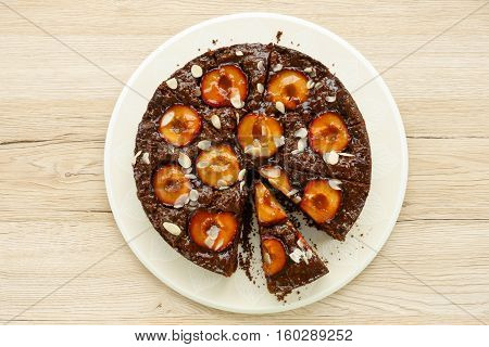 Whole Homemade Sticky Chocolate Plum Cake isolated on light brown wooden background.
