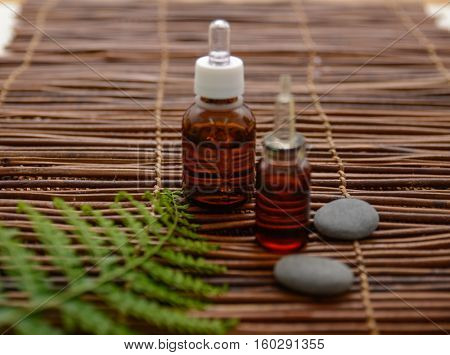 Fern with massage oil and massage ball ,stones, on mat