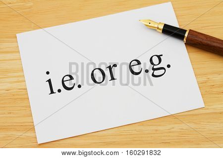 Learning to use proper grammar A white card on a desk with a pen with words ie or eg