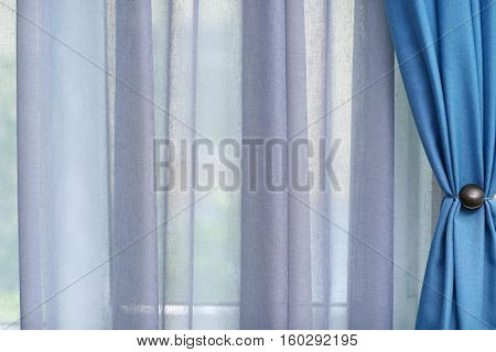 Room window with white and blue curtains, close up