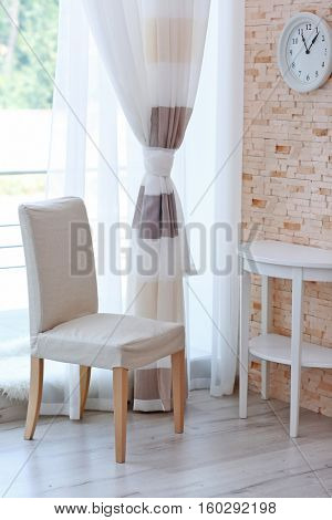 Chair, table and room window with colorful striped curtains
