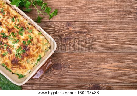 Chicken lasagna and white cheese on a wooden table .