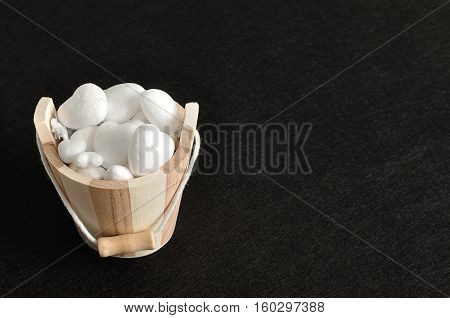 Valentines day. A wooden bucket filled with polystyrene hearts isolated against a black background