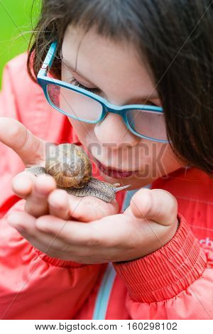 Smiling Little Girl Holding Garden Snail Gently