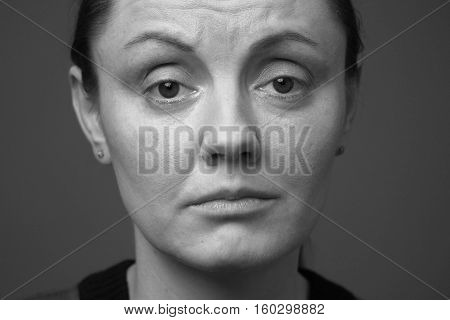 Close up woman's face looking grieved and disappointed black and white