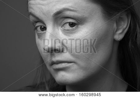 Close up pensive adult woman's face with big sad eyes half turned view black and white