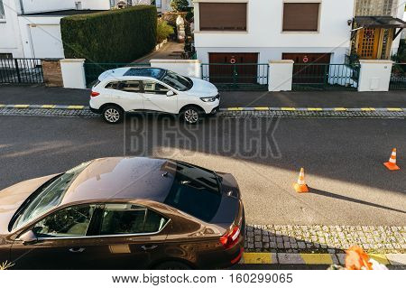 PARIS FRANCE - NOV 29 2016: Renault Kadjar and Skoda Ocatavia cars parked in front of a house early in the morning with safety cones during construction works