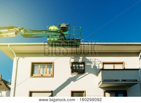 Modern hydraulic mobile construction platform elevated on the last floor of a house with construction worker preparing to to work